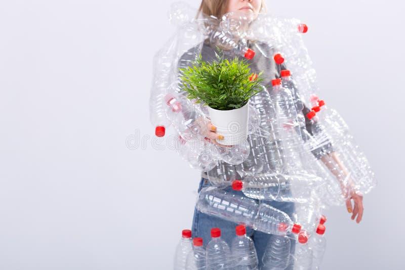 关闭妇女站起来与在塑料瓶的礼服并且拿着绿色植物 环境污染问题 库存照片