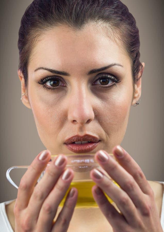 关闭妇女饮用的茶反对棕色背景 免版税库存照片