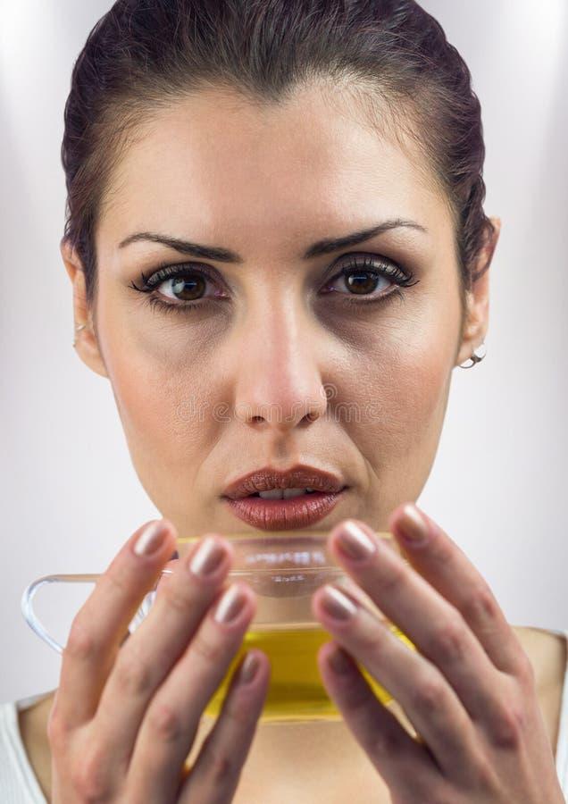 关闭妇女饮用的茶反对白色背景 免版税图库摄影