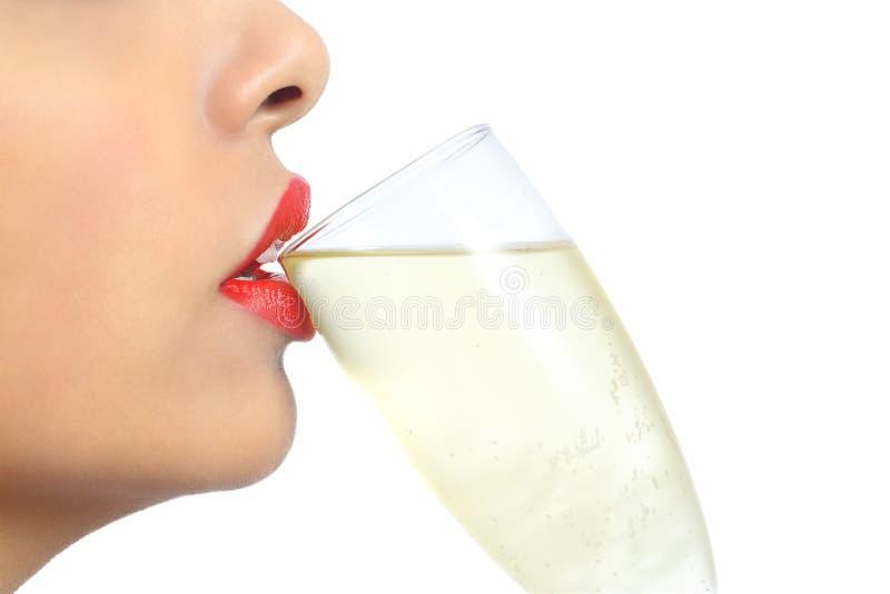 关闭妇女嘴唇的外形用红色唇膏饮用的香槟 免版税图库摄影