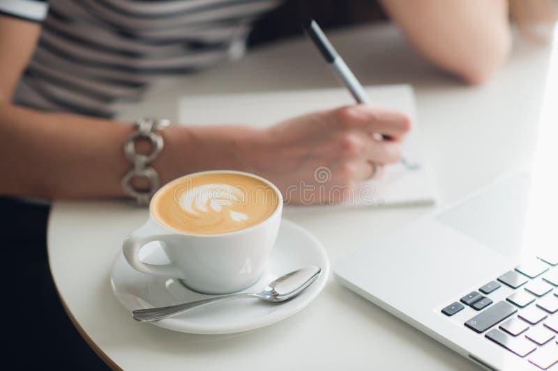 关闭妇女` s手和一个杯子的图片热奶咖啡 夫人在她的有附近的膝上型计算机的笔记本书写 库存照片
