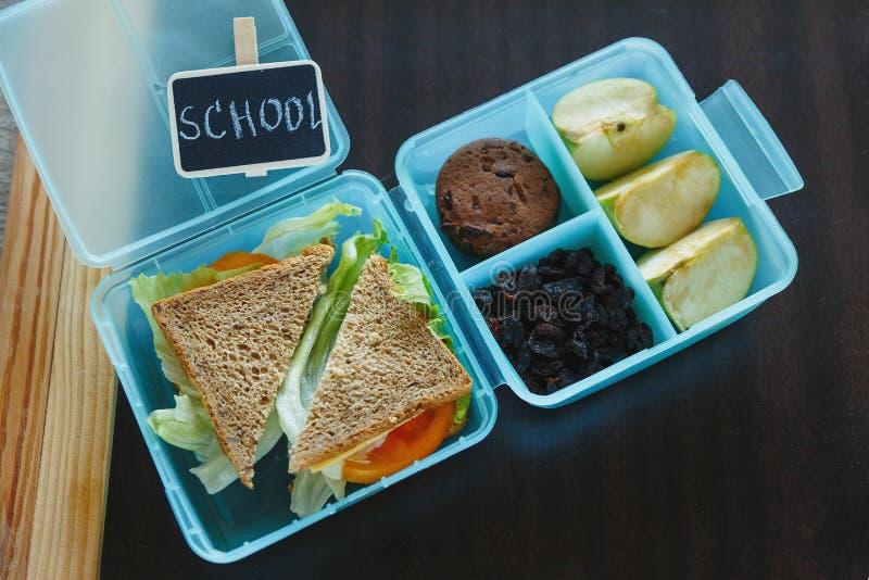 关闭学校蓝色饭盒用自创三明治,绿色苹果,曲奇饼,在黑黑板 健康吃在学校 库存照片