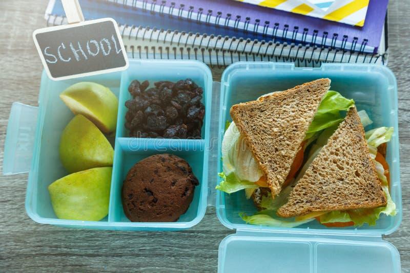 关闭学校蓝色饭盒用自创三明治,绿色苹果,曲奇饼,在黑黑板 健康吃在学校 免版税图库摄影