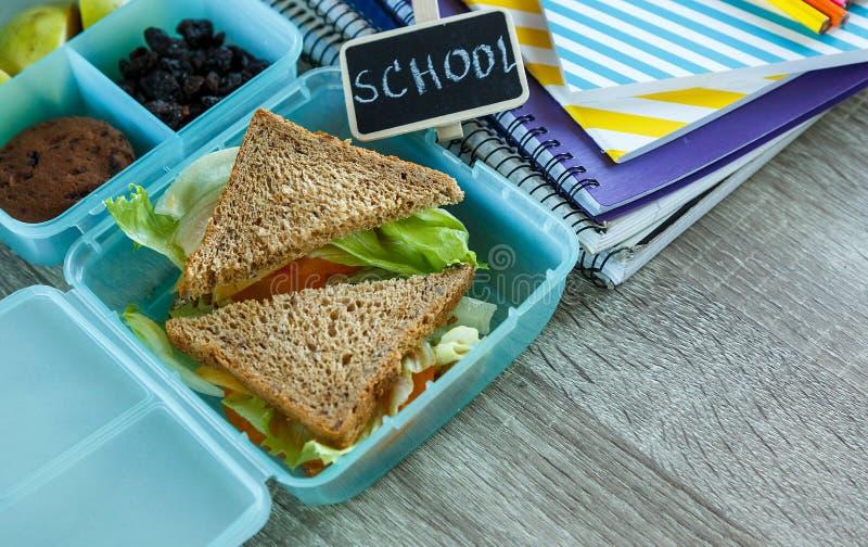 关闭学校蓝色饭盒用自创三明治,绿色苹果,曲奇饼,在黑黑板 健康吃在学校 库存图片