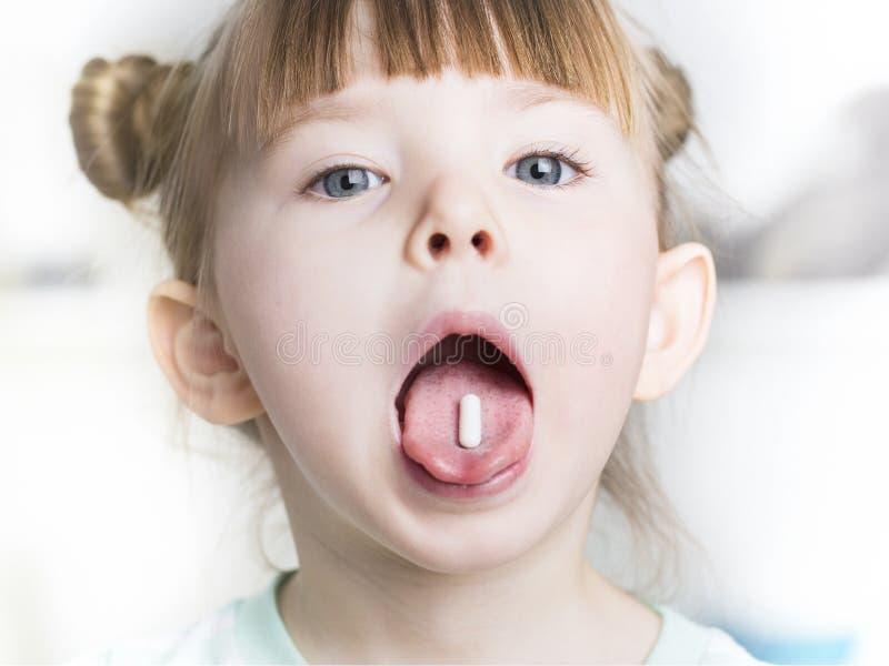 关闭孩子在他的嘴举起药片 免版税库存照片