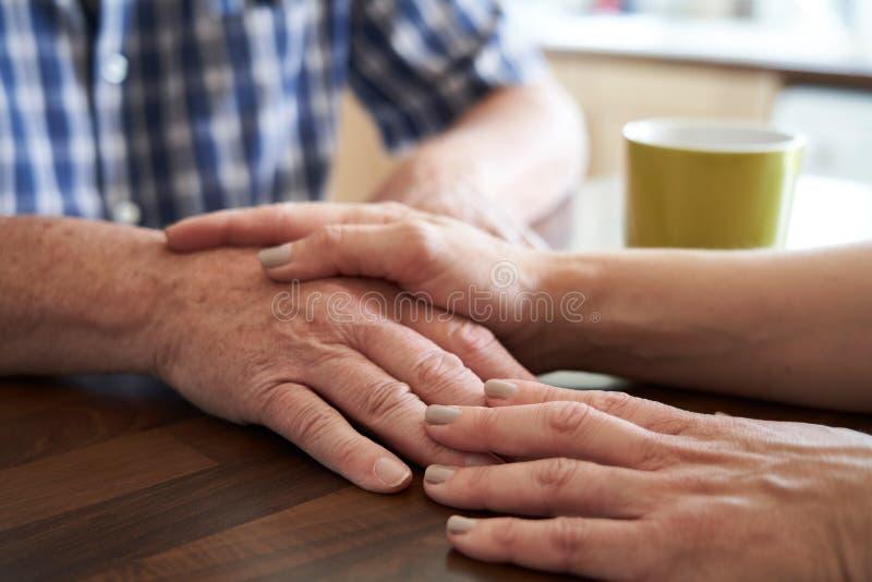 关闭安慰不快乐的老人的妇女在家坐在厨房里 库存图片