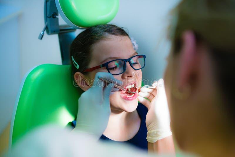 关闭安排的女孩他的牙审查由牙齿的牙医- 免版税库存图片