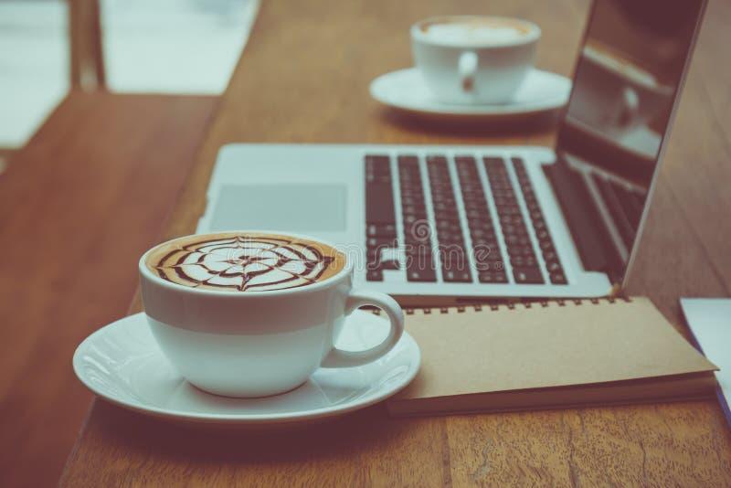 关闭安置与膝上型计算机一起的充分的咖啡杯在书桌 库存照片