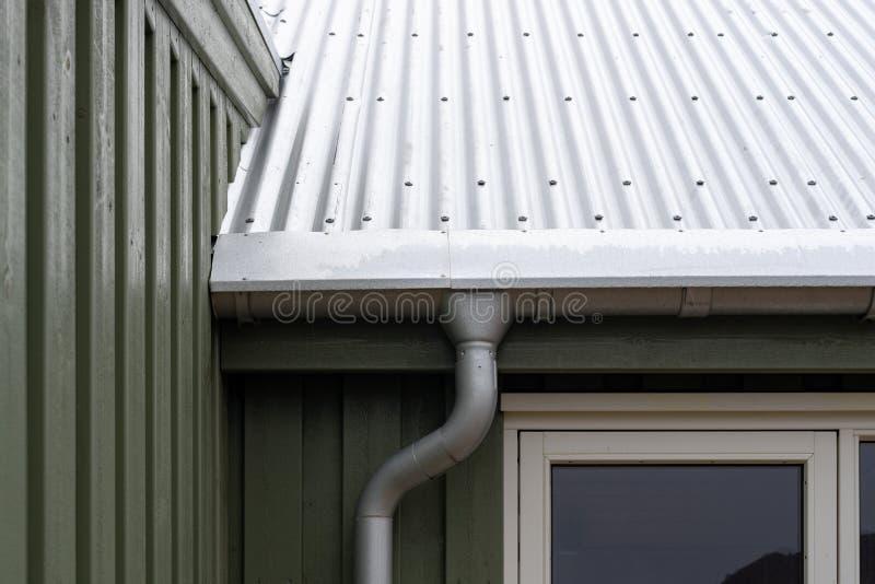 关闭小温室播种的照片有锌金属雨天沟的在檐口在铆钉屋顶下 免版税库存照片