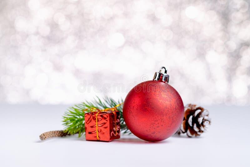 关闭小组红色圣诞节光滑的球和礼物盒在丝毫 图库摄影