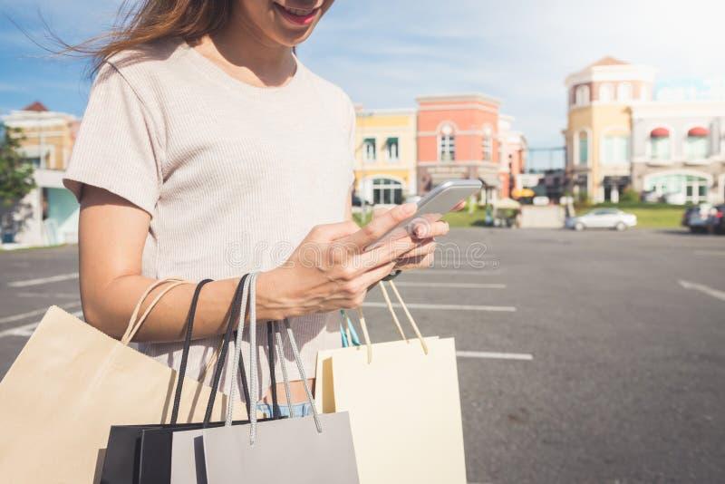 关闭少妇举行购物袋在她的手上和聊天在她的在购物以后的电话 免版税图库摄影