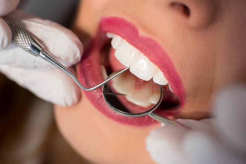关闭少妇有牙齿检查在牙齿办公室 牙医有牙齿工具的审查的患者` s牙 库存图片