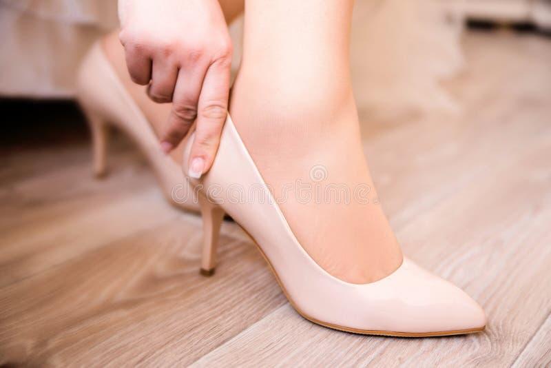 关闭尝试在新的鞋子的一名年轻老练妇女 库存图片