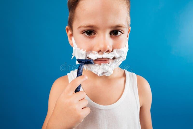 关闭尝试微笑的年轻的男孩的图片刮面孔 免版税库存图片