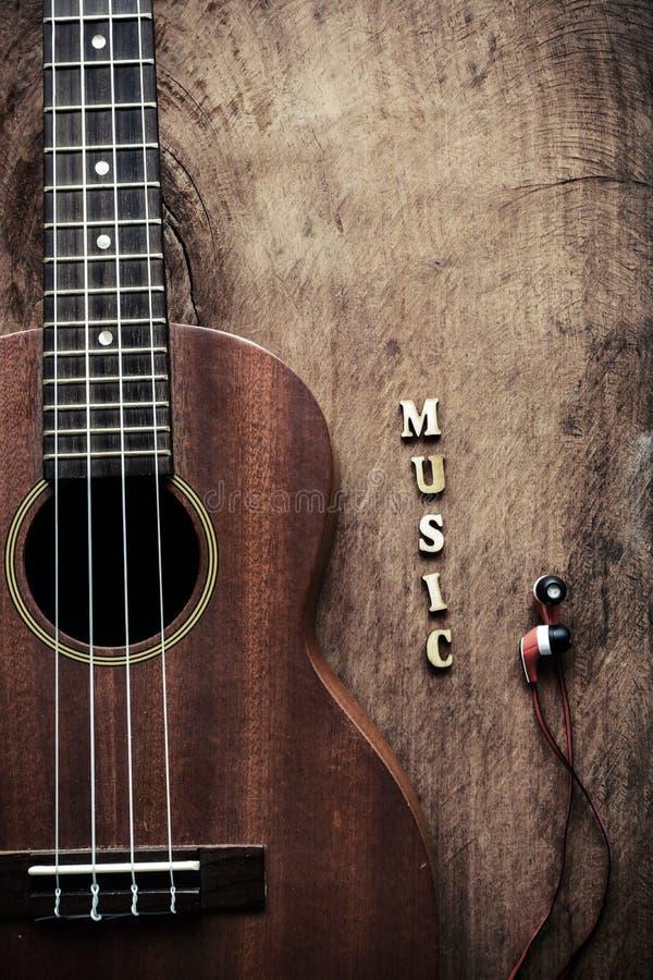 关闭尤克里里琴和耳机在老木背景 免版税库存照片