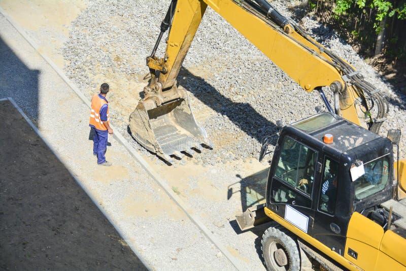 关闭工业挖掘机工作的细节在工地工作的 挖掘机桶在车行道的水平石渣 人在 图库摄影