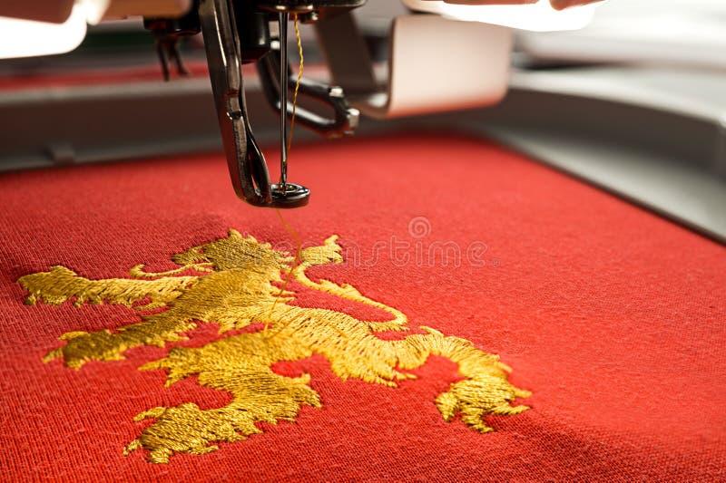 关闭工作区刺绣机器和金狮子设计的图片 免版税库存图片