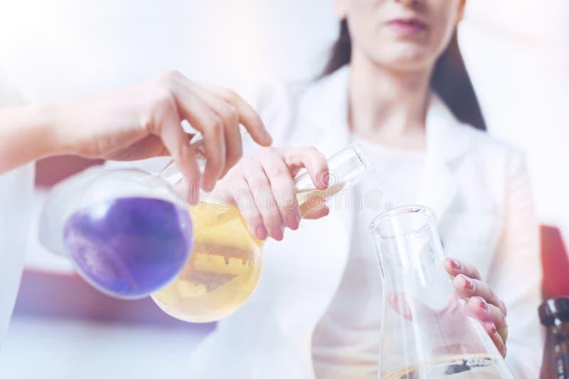关闭工作在化学实验室的老师和学生 库存照片