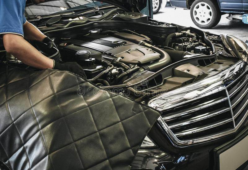 关闭工作在汽车修理的引擎的男性汽车机械师 图库摄影
