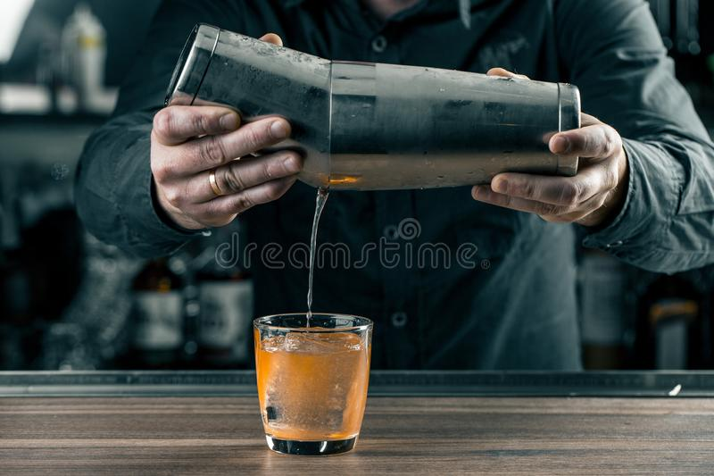 关闭工作的侍酒者细节  在冰的倾吐的柑橘鸡尾酒 免版税库存照片