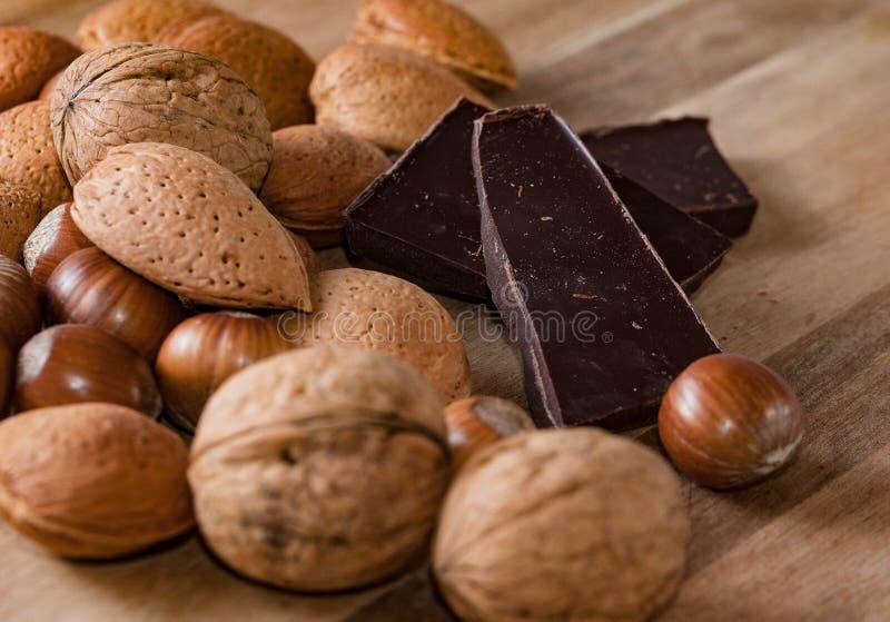 关闭巧克力被分类的坚果和pices在一个木选项的 免版税库存照片