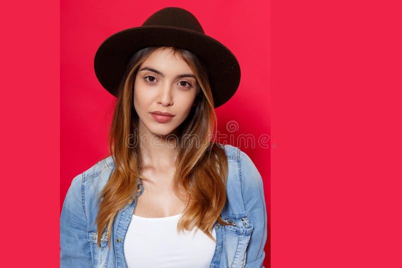 关闭帽子和牛仔布衬衣的一个热的深色的女孩,看与在照相机的态度,在红色背景 库存图片