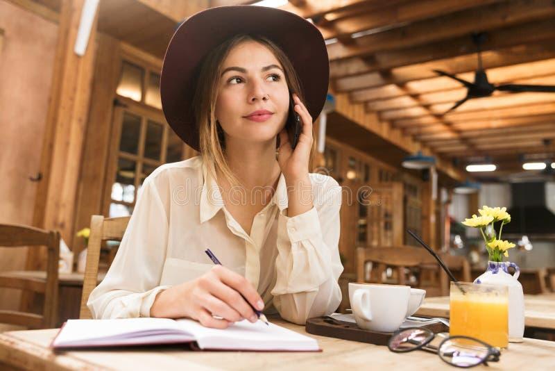 关闭帽子的一个俏丽的女孩在咖啡馆桌上户内,谈话坐手机,采取在笔记本的笔记, 免版税库存图片