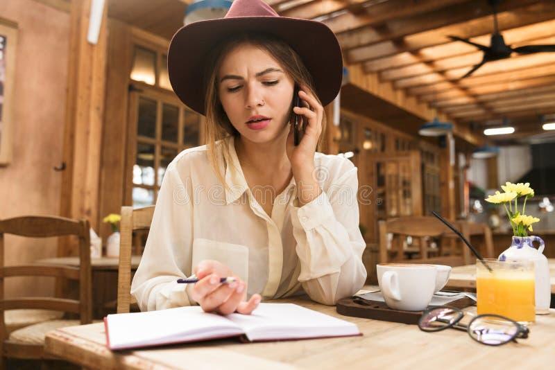关闭帽子的一个迷茫的女孩在咖啡馆桌上户内,谈话坐手机,采取在笔记本的笔记 免版税库存照片