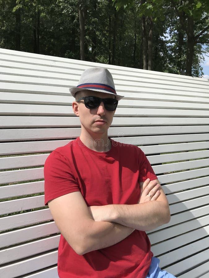 关闭帽子的白种人年轻人,红色T恤杉和太阳镜坐一条白色长凳在公园和神色入照相机 免版税图库摄影