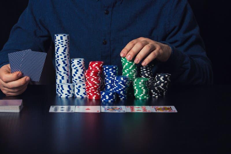关闭年轻人拿着卡片和打赌芯片的打牌者手在赌博娱乐场桌上 免版税库存照片