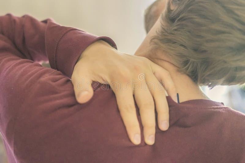 关闭年轻人接触脖子,并且后面遭受强的neckache g 库存照片