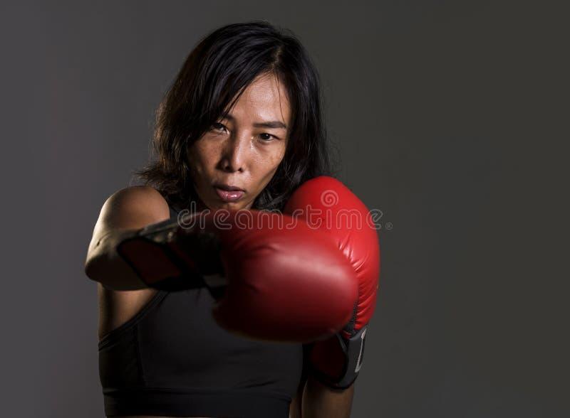 关闭年轻人适合亚裔中国妇女和挥在坏女孩态度的拳击手套画象健身上面的拳恼怒和 图库摄影