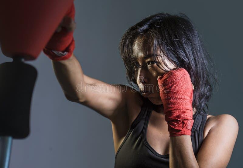 关闭年轻人适合亚裔中国妇女和挥在坏女孩态度的拳击手套画象健身上面的拳恼怒 库存照片