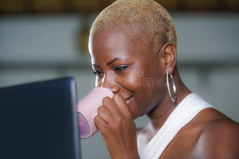 关闭年轻优等的可爱和愉快的黑人非裔美国人的运作在la的妇女饮用的咖啡或茶生活方式画象  免版税库存照片