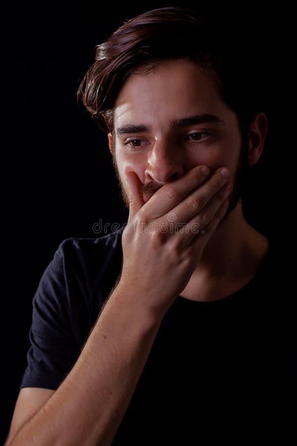 关闭年轻成年男性眼睛打开移交在震动或恐怖的嘴 剧烈的作用的深刻的颜色口气,黑暗和喜怒无常 图库摄影