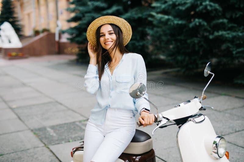 关闭年轻时髦的女人的生活方式图象偶然成套装备的坐在街道上的滑行车 佩带的蓝色衬衣,白色p 库存照片