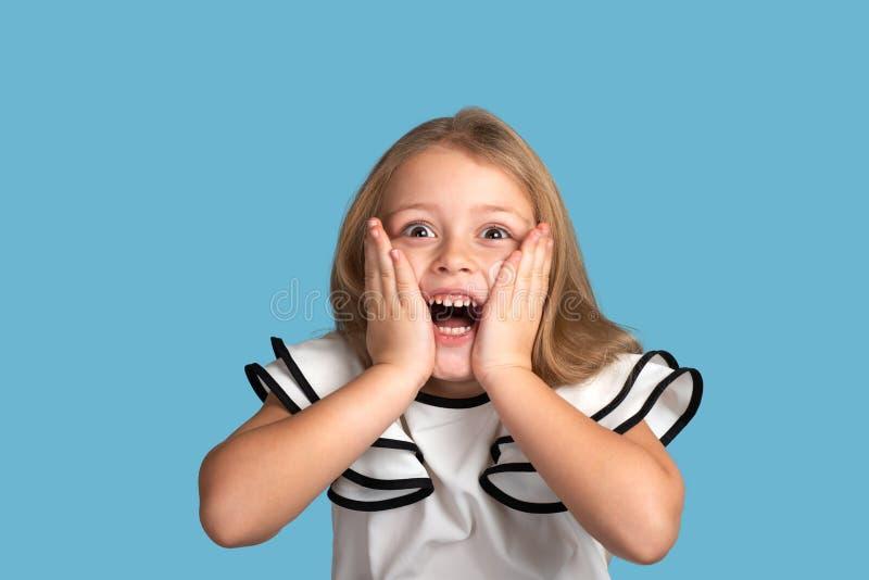 关闭年轻白肤金发的微笑的女孩情感画象蓝色背景的在演播室 她 免版税库存照片