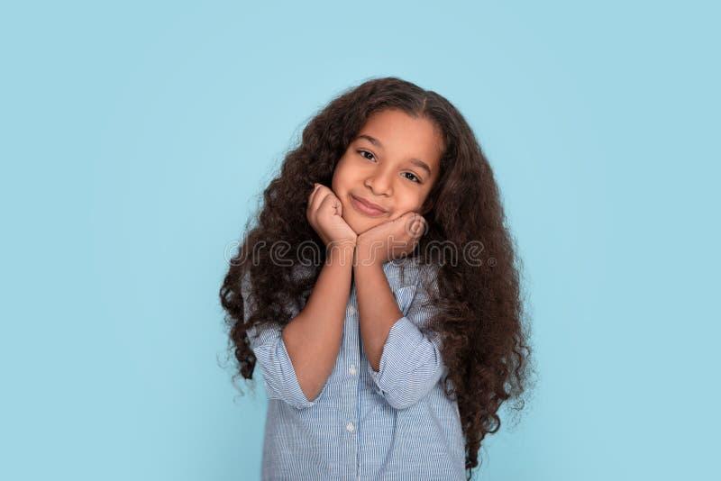 关闭年轻穿在蓝色背景的mulatta卷曲的微笑的女孩情感画象蓝色衬衣在演播室 她拿着她 免版税库存图片
