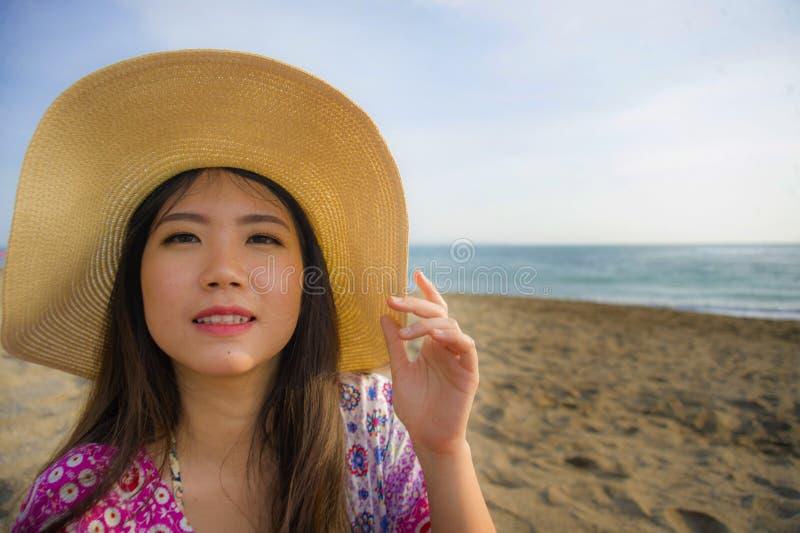 关闭年轻美丽和愉快的亚裔韩国旅游妇女生活方式画象夏天帽子微笑的快乐对热带isl 免版税库存照片