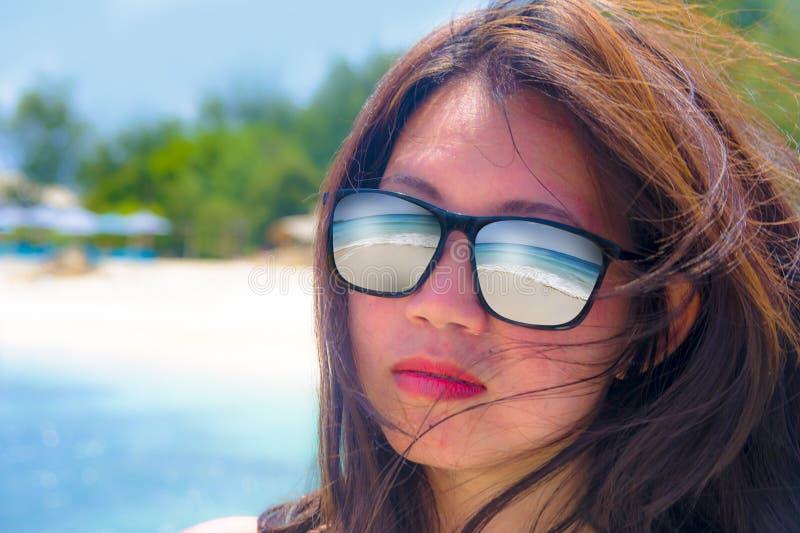 关闭年轻美丽的亚裔有热带海滩海的妇女佩带的太阳镜面孔画象并且铺沙在glasse的反射 免版税库存照片