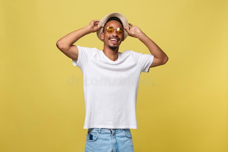 关闭年轻美国黑人震惊游人画象,拿着他的eyewear,佩带的旅游成套装备,帽子,有宽的 库存图片