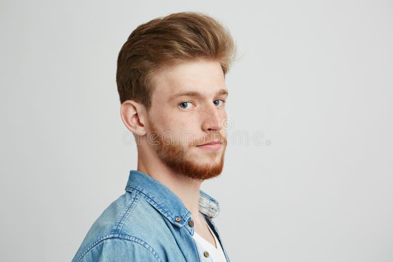 关闭年轻英俊的行家人画象有看在白色背景的胡子佩带的斜纹布衬衣的照相机 图库摄影