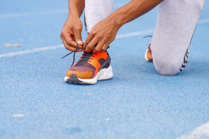 关闭年轻黑人运动员人的手和腿选择聚焦栓跑鞋的在室外的公园 免版税库存图片