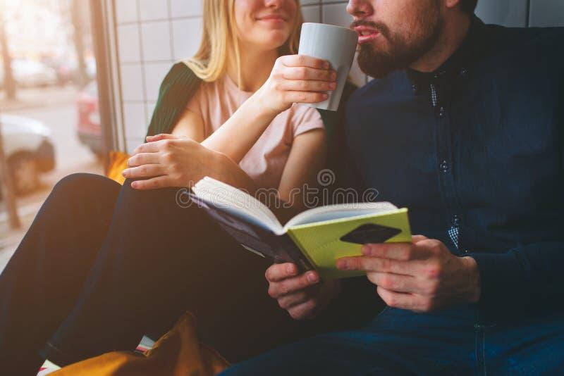 关闭并且削减坐在咖啡馆的观点的男孩和女孩在大窗口附近 她喝着一些coffe并且给她的杯子 免版税库存照片