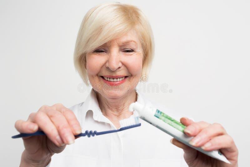 关闭并且削减把一些牙膏放的妇女的vuew在牙刷上 她要清洗她的牙 夫人是 免版税库存图片