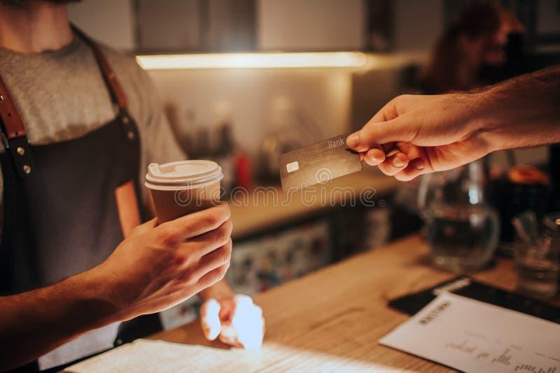 关闭并且削减拿着一杯咖啡和给它的男服务员手的看法顾客 同时 库存图片