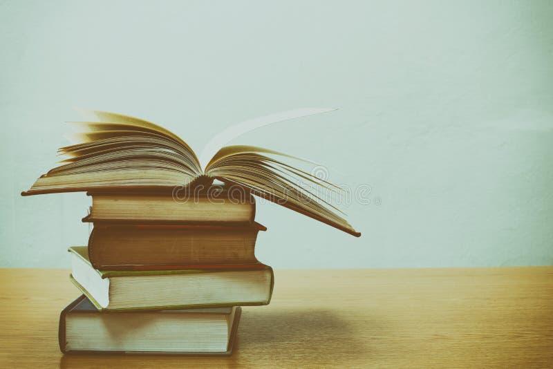 关闭开放书和堆在书桌上的书有葡萄酒过滤器迷离背景 图库摄影