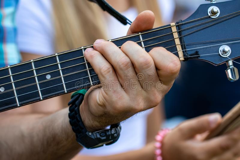 关闭弹吉他的人手 实践在弹吉他 图库摄影