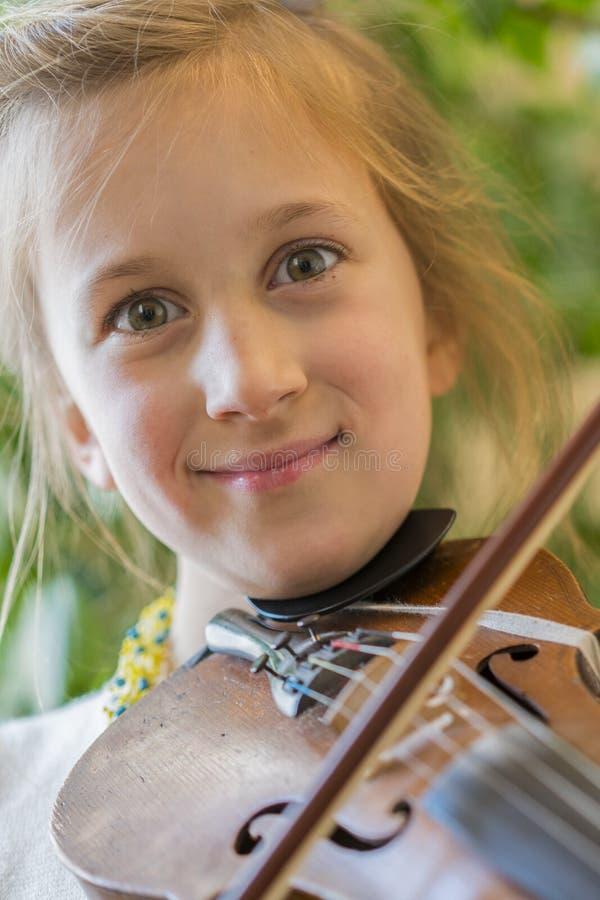 关闭弹在绿色背景的孩子小提琴 r 画象小 库存照片