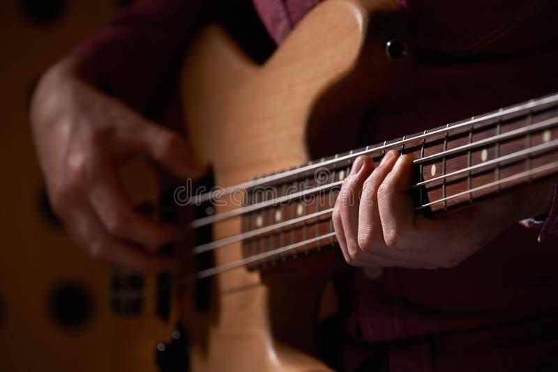关闭弹奏仪器的低音吉他弹奏者 免版税库存图片